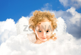 little girl with fairy wings lies on a cloud