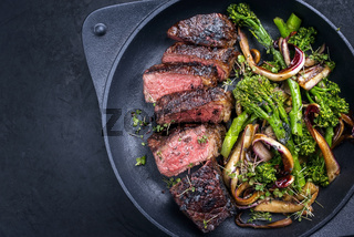 Modern style barbecue dry aged wagyu Brazilian picanha steaks from the sirloin cap of rump beef with rapini broccoli rabe and caramelized radicchio tardivo served as top view in a design skillet with copy space left