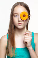 Teenager girl with with flower lollipop in hands closing eye.