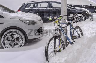 Winter in der Stadt - Autos und Fahrrad abgestellt und zugeschneit.