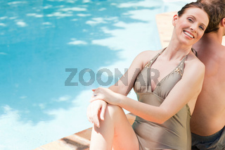 Couple sitting beside the swimming pool back to back