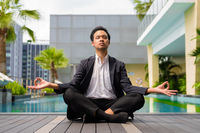 Asian businessman wearing suit and doing yoga and meditation next to swimming pool
