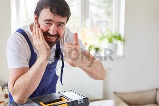 Lächelnder Mann als Handwerker mit Daumen hoch