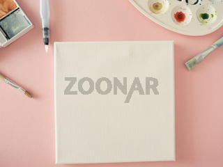 Invitation concept with a blank canvas and watercolors and brushes on a pink background