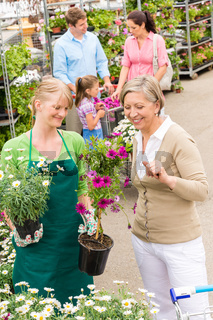 Customer at garden centre buying potted flowers