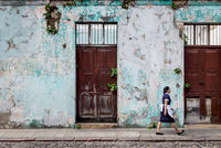 Local maid walking along an abandoned colonial building with plants growing out of the cracked walls, Antigua, Guatemala