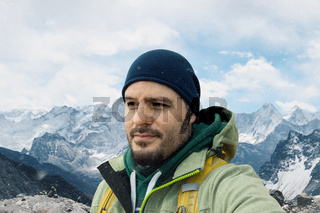 Man with backpack trekking in mountains. Cold weather, snow on hills. Winter hiking portrait