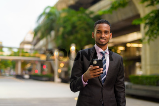 Young African businessman outdoors in city using mobile phone