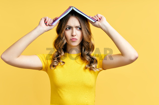 Photo of funny woman holding book over head, confused expression