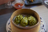 Three Chinese green dumplings in a traditional bamboo steamer