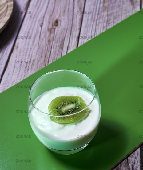 Glass of yoghurt with a sliced kiwi