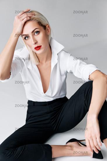 Fashion portrait of sensual trendy woman posing sitting on floor on white studio background
