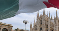 the Italian flag flapping above the Milan Duomo cathedral.