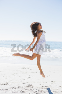 Happy brunette in white sun dress dancing on the sand
