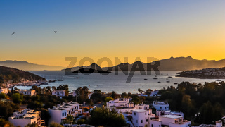 Bright colorful sunset in the beautiful bay of the Aegean sea with islands, mountains, boats and birds in the sky . Summer holiday concept and travel background