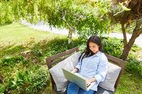 Frau arbeitet am Laptop im grünen Garten als Freelancer