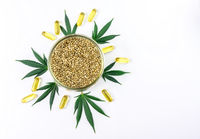 Bowl with Hemp seeds Cannabis leafs and CBD oil capsules isolated on white