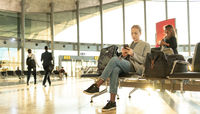 Casual blond young woman using her cell phone while waiting to board a plane at airport departure gates.