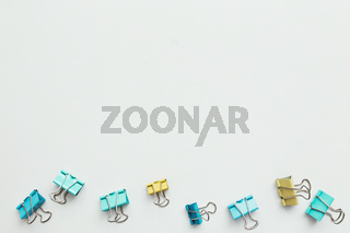 Blue and yellow paper clips on white background. Work and education concept