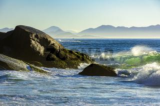 Waves crashing against the rocks at summer dawn on Devil beach in Ipanema