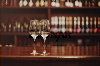 Two glasses of white wine on the wooden bar table