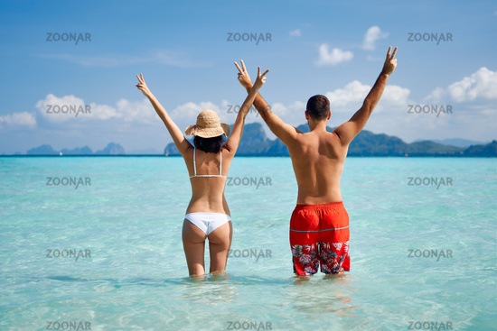 Rear view of happy couple with hads up enjoying warm tropical ocean water.