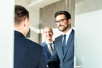 Group of cheerful confident business people greeting with a handshake at business meeting in modern office.