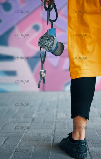 Cropped image of street artist with respirator mask in hand