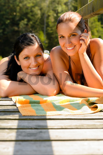 Mother and daughter sunbathing on pier smiling