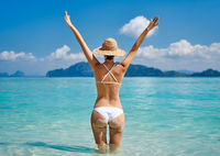 Rear view of a beautiful happy girl with raised hands enjoy her tropical beach vacation
