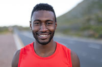 Portrait of fit african american man standing on a coastal road looking at camera smiling