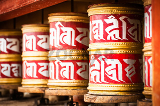 Buddhist prayer wheels in Tibetan monastery with written mantra. India, Himalaya, Ladakh