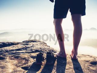 Slim male legs in strong backlight. Barefoot man hiker feet climbing