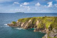 Beautiful emerald water of Atlantic Ocean and tall cliffs near Dunquin Pier, Dingle