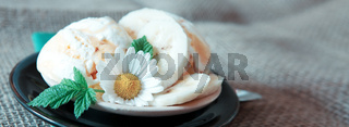 Ice cream with bananas on black plate.