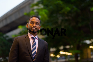 Portrait of handsome young African businessman smiling outdoors in city