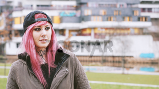 woman with pink hair at social housing estate
