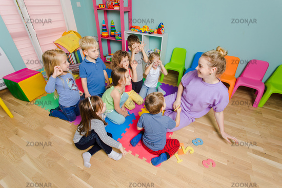 Preschool teacher teaching group of children, sitting on a floor