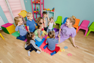 Preschool teacher teaching group of children, sitting on a floor