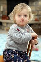 kleines Mädchen sitzt im Wohnzimmer auf einem Kinderstuhl aus Holz und zieht eine Schnute