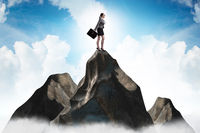 Businesswoman at the top of mountain in career concept