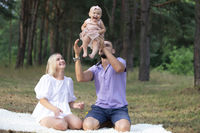 Husband, wife and their little daughter for a walk in the park. Happy dad and mom toss up their little daughter.
