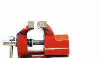 close-up view of a red steel bench vise isolated on a white background