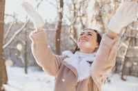 Delighted female playing with snow on street