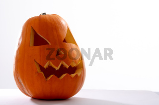 Composition of scary halloween carved orange pumpkin on white background