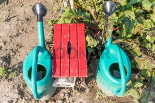 Gießkannen und Hocker im Schrebergarten - Gartenarbeit