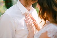 The groom hugs gently kisses the bride on the forehead, the bride puts her hands on grooms chest