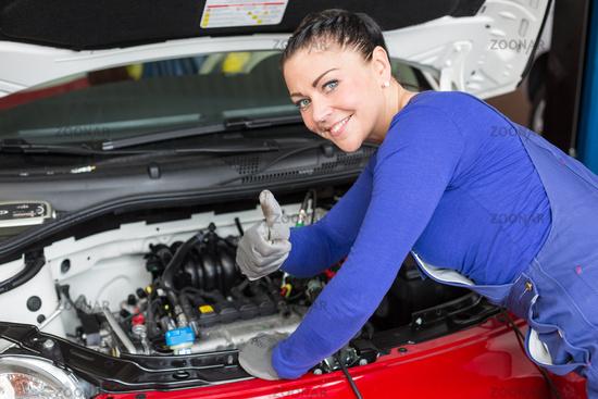Kfz Mechanikerin repariert ein Auto