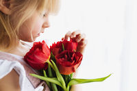 Smiling small girl holding bouquet of red tulips. Concept for greeting card
