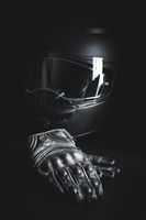Black leather motorcycle gloves and helmet on black background.